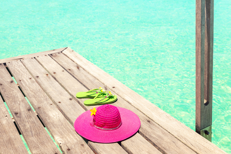 Large pink sun hat and sandal on the deck by the sea