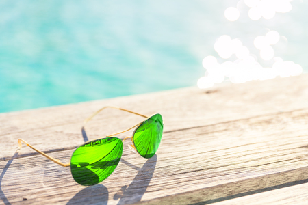 Green Sunglasses on a wooden deck, summer holiday concept Stock Photo