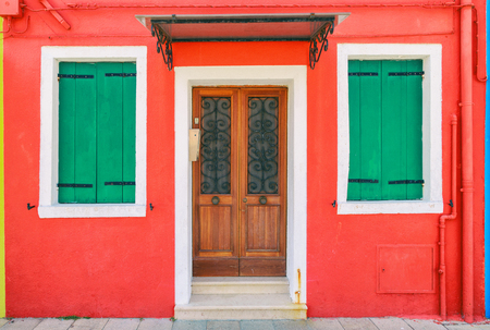 Picturesque windows with shutters of red house on the famous island Burano, Venice, Italy Stock Photo