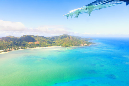 Aerial view of Mahe, maine island of Seychelles, with part of airplane wing