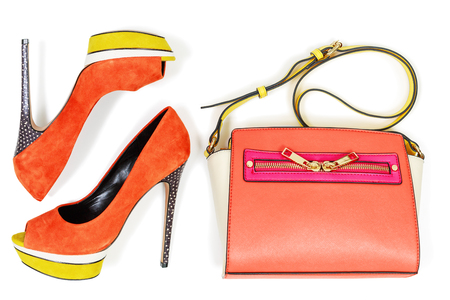 Pare of peep toe orange and yellow high hilled platform pump shoes and matching bag,  isolated on white background, top view