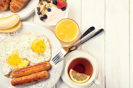 Breakfast with sunny side up eggs, sausages, orange juice, and fruits on white wooden background