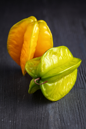 ripe yellow and green star fruit carambola or star apple ( starfruit ) on dark wooden background