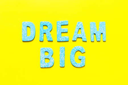 Word DREAM BIG  made out of small blue wooden letter on yellow background