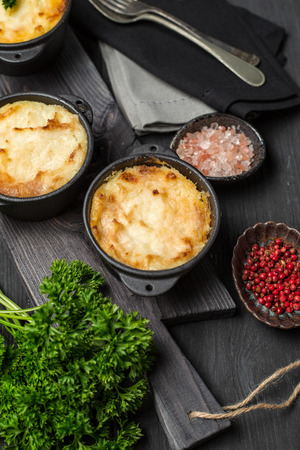 Shepherds pie, british casserole in cast iron pan, with minced meat, mashed potatoes and vegetables, on dark background, vertical composition
