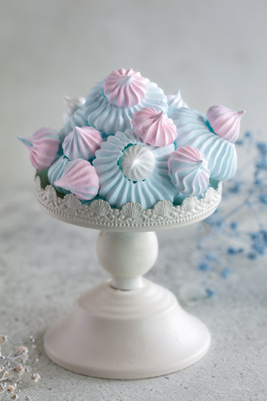 Homemade pastel pink, blue and white meringue on small metal cake stand, vertical composition