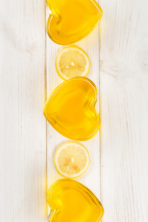 Yellow lemon jelly in heart shaped glass on white wooden background, top view, vertical composition