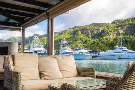 Resting corner with view of Luxury yachts and Boats in sunny summer day at marina of Eden Island, Mahe, Seychelles
