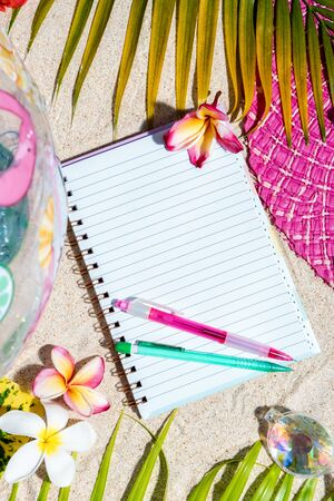 Open blank writing note pad with pink and green pen on sand, surrounded by green palm leafs, sea shells, pink hat, inflatable toys. Summer beach background, flat lay, vertical composition
