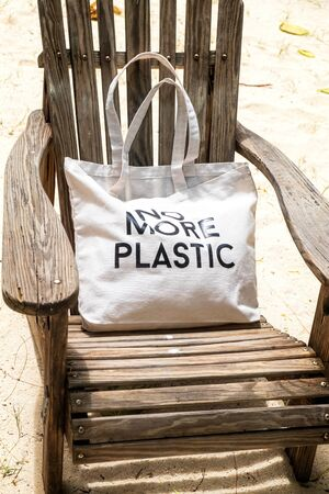 Eco bag with sign NO MORE PLASTIC on wooden beach chair, vertical composition