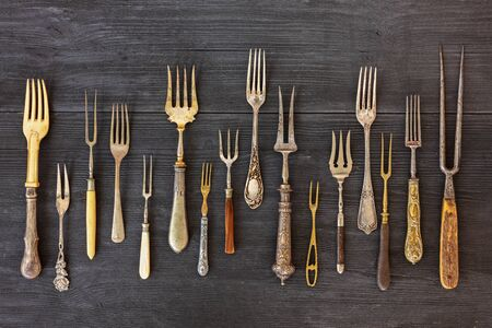 Vista dall'alto su varie forchette, vecchi utensili. Piatto giaceva su fondo di legno rustico. Sfondo di utensili da cucina antichi