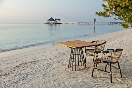 Elegant table and two chairs on sandy beach, romantic vacations background