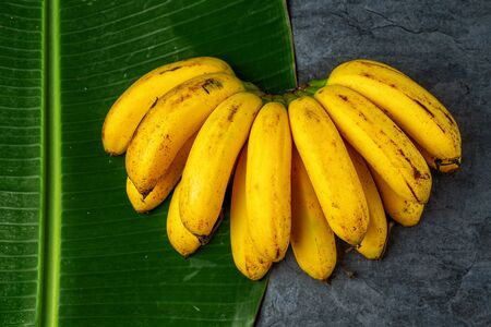 Bunch of fresh bananas on banana leaves, top view Stock Photo
