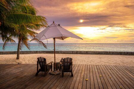 Sonnenschirm und Liegestühle am wunderschönen tropischen Strand und Meer bei Sonnenuntergang für Reisen und Urlaub