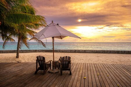 Umbrella and deck chairs on the beautiful tropical beach and sea at sunset time for travel and vacation 免版税图像