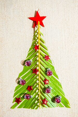 Christmas tree made of green palm thee brunch with small red festive decorations on sand, top view, vertical composition