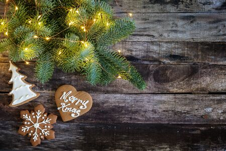 Ginger bread cookies and Christmas tree brunch with lights on wooden background, flat fay, copy space