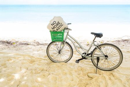 Lonely vintage bicycle on the tropical sandy beach  with No More Plastic bag in the basket with sky and calm sea at background, copy space