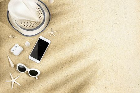 White hat, sunglasses, phone, headphone, sea shells and starfish with palm branch shadow on sand background, copy space, flat lay