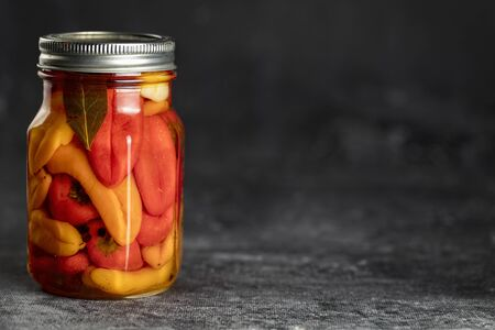 Jar of pickled mix bell peppers and spices. Fermented food on dark background, copy space Standard-Bild