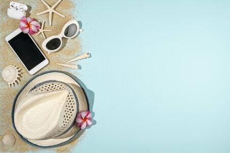 Summer holiday concept with white hat, sunglasses, phone, headphone,  sea shells and starfish on light blue background and sand, copy space, flat lay