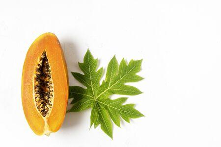 Ripe freshly cut papaya fruit with green papaya leaf on white background, flat lay, copy space, isolated
