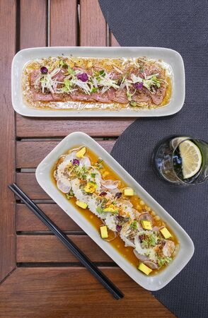 Two plates with Tuna and red snapper Carpaccio, candid light, top view , vertical composition