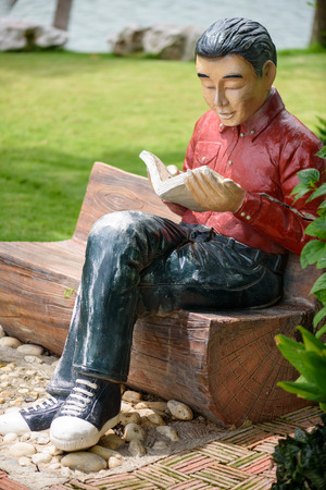 stucco: Doll stucco reading book Stock Photo
