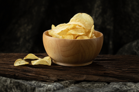 potato chip crisp in wood bowl on wood background  unhealthy cause of fat but delicious  snack Stockfoto