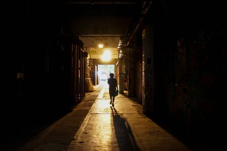 The back in the tunnel walks towards the light Banco de Imagens