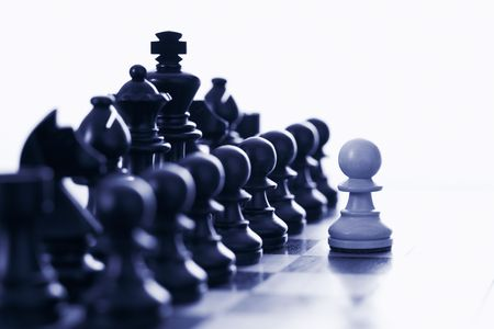 White pawn challenging army of black chess pieces blue tone