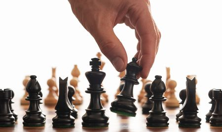 Chess board and hand picking up the queen on a white background
