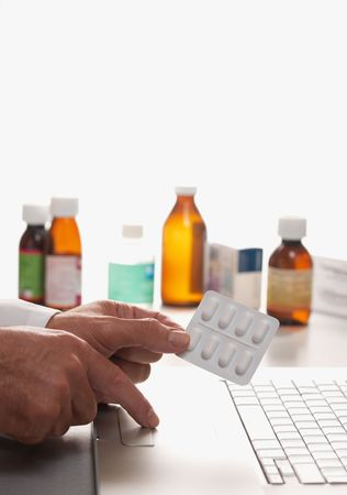 Pharmacist holding Prescription with laptop computer