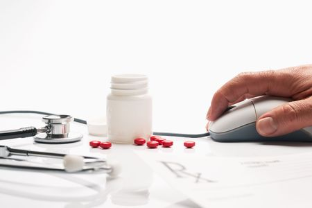 Prescription medicine and pharmacist hand on computer mouse in pharmacy with pill bottles in background