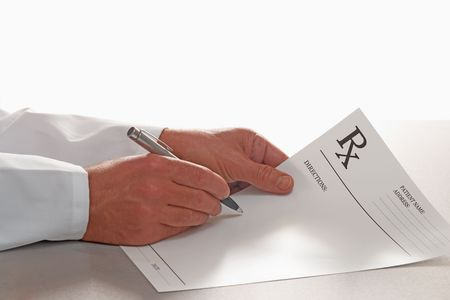 medical report: Doctor writing out prescription on RX form on white background  Stock Photo