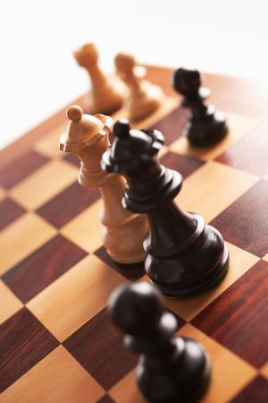 chess back and white queens face each other selective focus