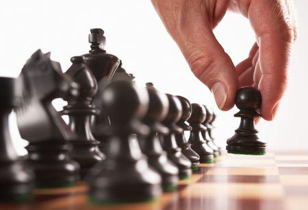 tablero de ajedrez: jugador de ajedrez negro primer paso la mano se mueve pe�n enfoque selectivo