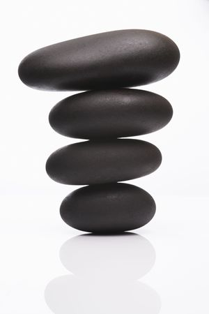 spa stones in perfect balence on reflective white background