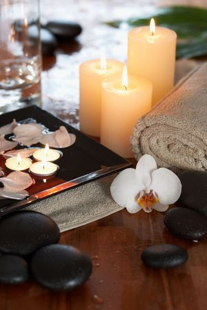scented candle: relaxing spa with candles orchids towels and stones on wooden background  Stock Photo