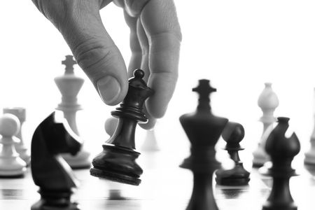 Chess game black queen advances b&w close up of hand