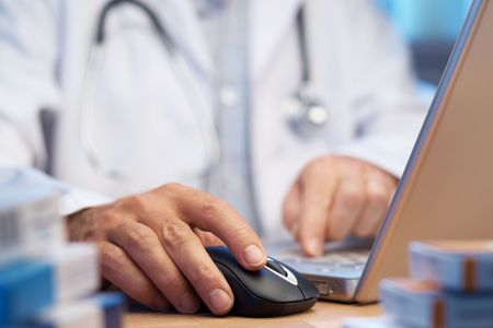 Doctor preparing online internet prescription selective focus  photo