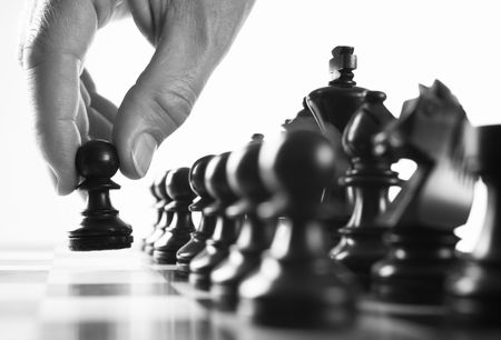 chess  player hand moves pawn selective focus black and white Stock Photo