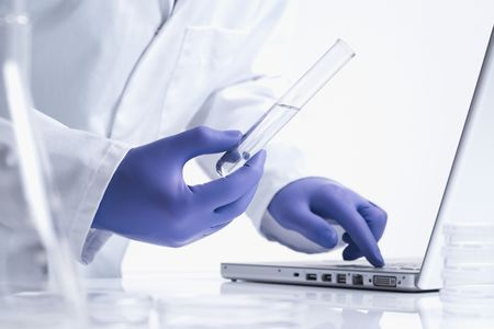 scientists: scientist entering data on laptop computer with test tube white background  Stock Photo
