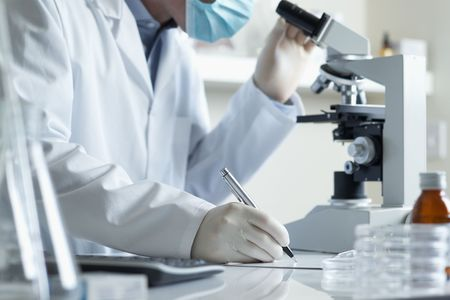 lab test: Scientist conducting research taking notes whilst looking through microscope selective focus  Stock Photo
