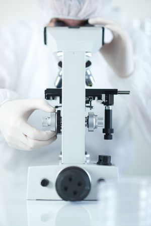Scientist conducting research in sterile laboratory whilst looking through microscope selective focus