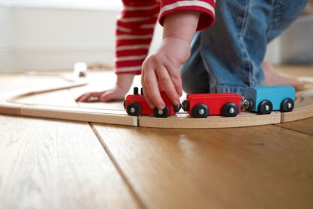 Child playing with toy wooden train selective focus