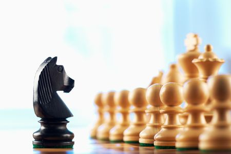 checkmate: Chess black knight challenges white pawns abstract background  Stock Photo