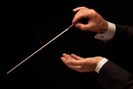 orquesta: Director de orquesta dirigiendo una orquesta aislada sobre fondo negro