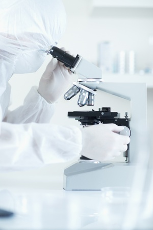scientist in sterile environment with microscope selective focus