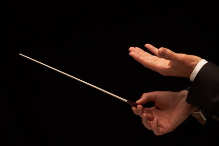 louder: Concert conductor hands with baton isolated on black background  Stock Photo